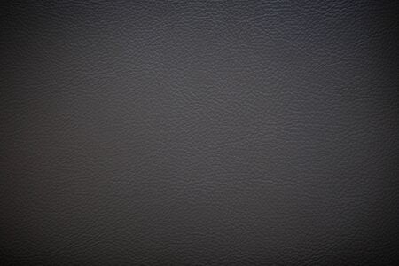 Surface of dark gray faux leather with vignette for textured background