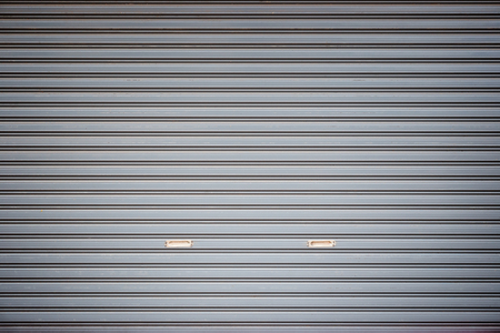 Full frame background of a closed roller door (or roller shutter, sectional overhead door, roll up or rolling garage door) with vignette.