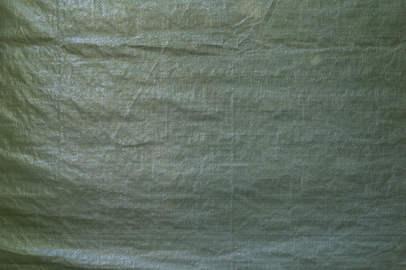 Full frame background of a wrinkled green tarp texture