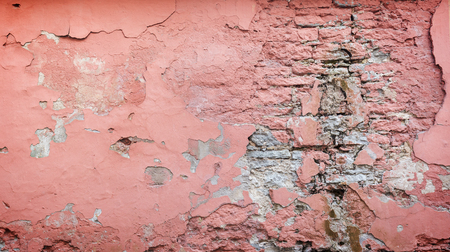 Full frame background of a weathered, damaged and plastered wall painted in pink. Plaster is partly peeled off revealing old bricks. Stock Photo