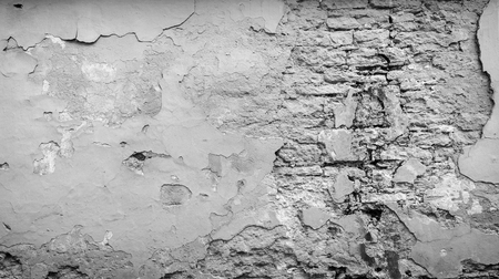 Full frame background of a weathered, damaged and plastered wall painted in black and white. Plaster is partly peeled off revealing old bricks.