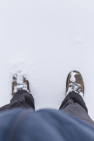 Low section of a person wearing outdoor clothes and shoes and standing on snow in the winter. Copy space.