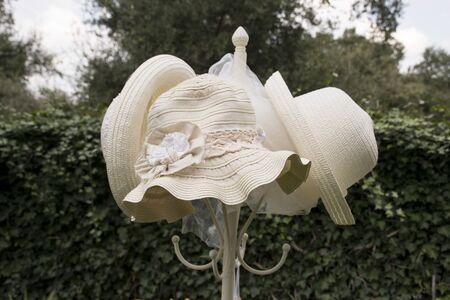 coat rack: Straw hat on a coat rack in a garden. vintage image Stock Photo