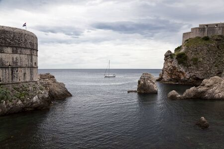 Sailing boat along the walls of Dubrovnik, medieval city in the adriatic coast photo