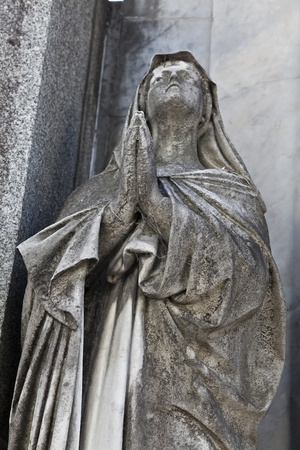 Sculpture of a woman praying at recoleta cemetery, Buenos Aires  Argentina photo