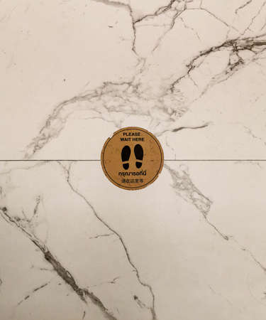 signage of foot print on brown circle background in the middle of marble floor black lines on white, with text please wait here Reklamní fotografie
