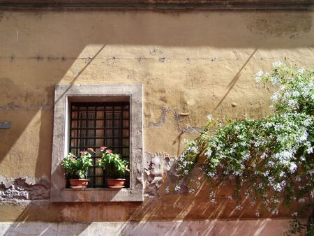 architectural architectonic: Small window with flower pots. Old Italian architecture in Rome. Stock Photo