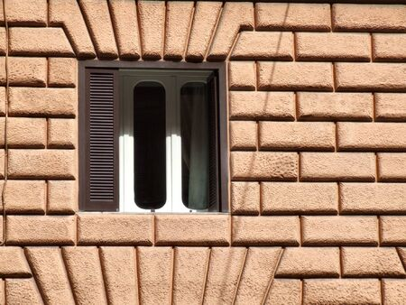 Interesting wall ornament and a single window in a Mediterranean town in Italy. Rome architecture. Stock Photo - 689067