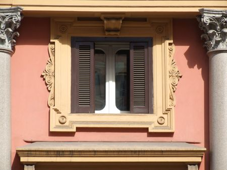 architectural architectonic: A window with yellow ornament around it. Historic building in Rome.