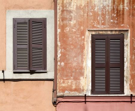 Two asymmetric windows with brown shutters - beautiful architecture detail in Rome, Italy. Stock Photo - 689085
