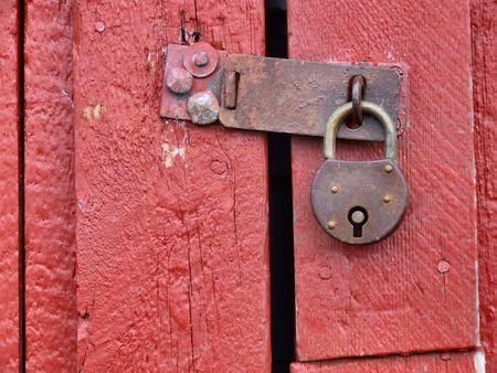 Old rusty padlock on a wooden door in Norway. Stock Photo - 689392