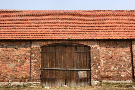 Old brick barn with wooden gate. Polish rural building. Countryside of Poland. Stock Photo - 891244