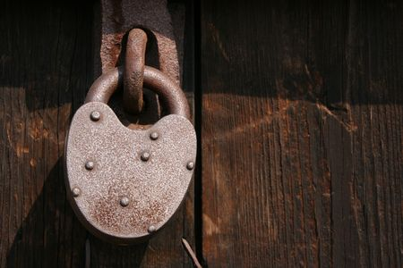 Old rusty pad lock on wooden door. Stock Photo - 891248