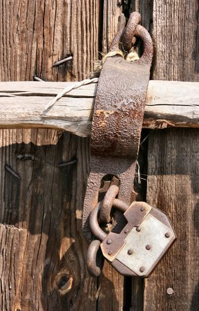 locked: Wooden door to a warehouse and a metal pad lock. Closed and secure. Stock Photo