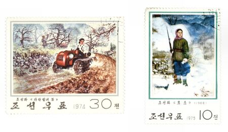 realism: Obsolete postage stamps from North Korea. Old collectible items - leisure and hobby collection. These post stamps show socialist realism concepts - women working in agriculture (driving a tractor) and a woman with gun (serving in the army). Stock Photo