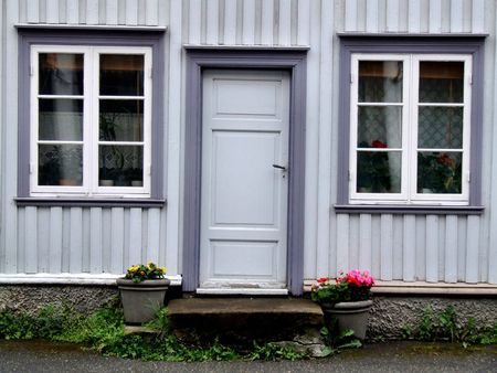Two windows, door and flowers. Front wall of a residential building. Stock Photo - 999458