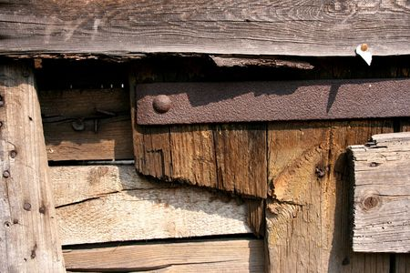 Old ruined barn - rural architecture. Declining planks, rusty metal bar and nails. Stock Photo - 1148420