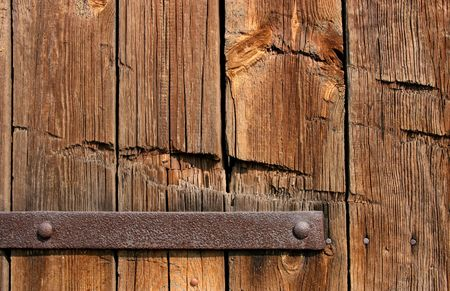 Old wood background texture. Vintage warehouse door and metal element. Rural architecture.