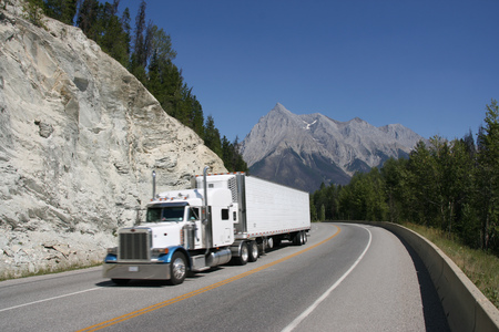 Trans Canada Highway - a truck speeding among rocky mountains.