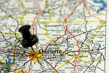 Charlotte, North Carolina. Push pin on an old map showing travel destination.