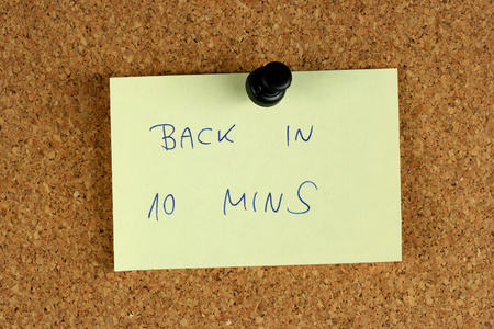 unavailability: Yellow small sticky note on an office cork bulletin board. Back in 10 minutes. Stock Photo