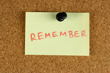 Yellow small sticky note on an office cork bulletin board. Remember message. Stock Photo - 1676225