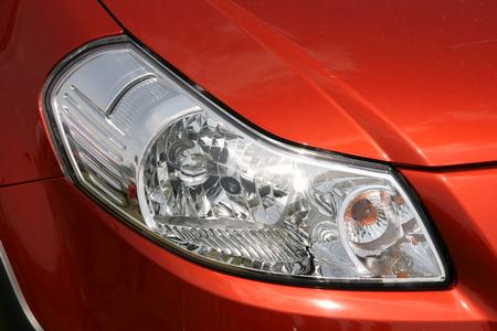 shiny car: Voorlicht van een nieuwe, oranje, glimmende auto Stockfoto