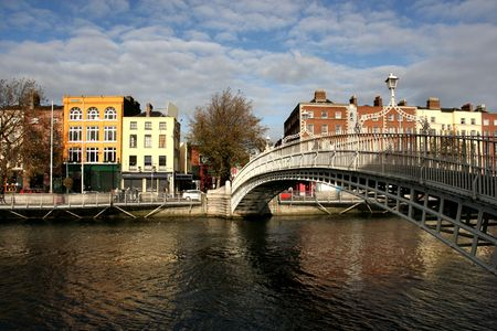 Dublin landmark - Hapenny bridge on Liffey River. Rows of colorful houses.