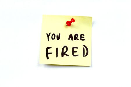 Yellow small sticky note on an office bulletin board. You are fired! Employment problem. Stock Photo - 2404439