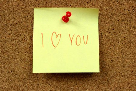 Yellow small sticky note on an office cork bulletin board. I love you confession. Stock Photo - 2625564