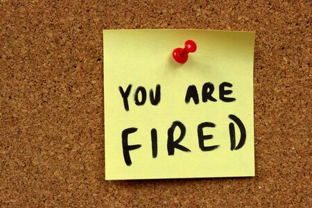 Yellow small sticky note on an office cork bulletin board. You are fired - unemployment and problems at job. photo