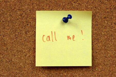 Yellow small sticky note on an office cork bulletin board. Call me! Urgent telephone contact needed. photo