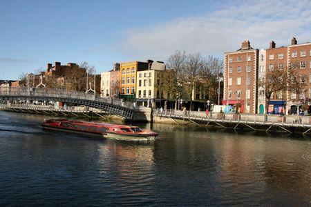liffey: Hapenny Bridge and Liffey river cruise boat in Dublin, Ireland. Typical view of Irish capital city. Stock Photo