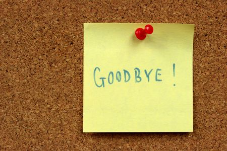 Yellow small sticky note on an office cork bulletin board. Goodbye message. photo
