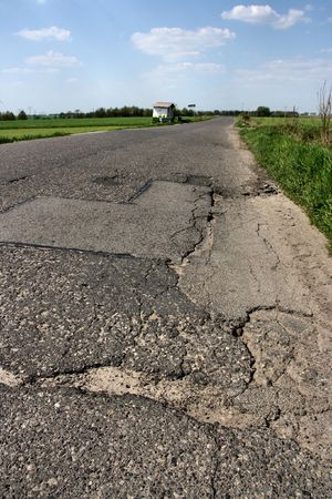 pothole: Road cracks - damaged asphalt with potholes in Polish countryside. Rural route.