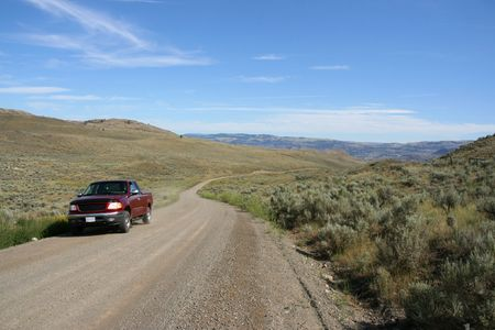 nowhere: Pickup truck on a gravel road in the middle of nowhere. Sagebrush hills in British Columbia, Canada.