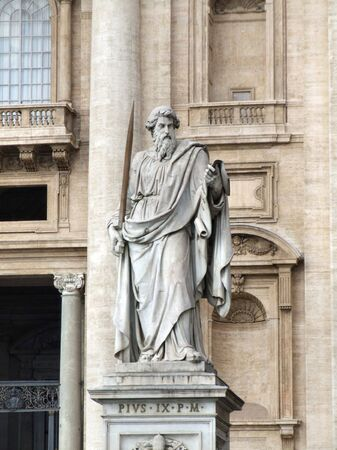 Statue of Saint Paul the Apostle, located on St. Peters Square in Vatican. Ordered by Pope Pius IX (the ninth). Famous St. Peters Basilica in the background.
