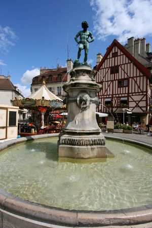 rude: Famous fountain, characteristic houses and colorful carousel in Dijon, Burgundy, France. Place Francois Rude. Stock Photo