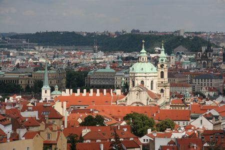 Cityscape of Mala Strana (Lesser Town) in Prague, Czech Republic. Beautiful baroque St. Nicolas Church is in full sun, whereas most of other buildings are in shade. photo
