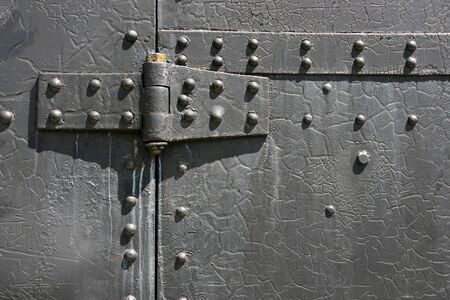 Industrial steel tin door texture. Metal hinge and bolts. Stock Photo