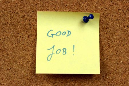 Yellow small sticky note on an office cork bulletin board. Good job - motivating and positive message.