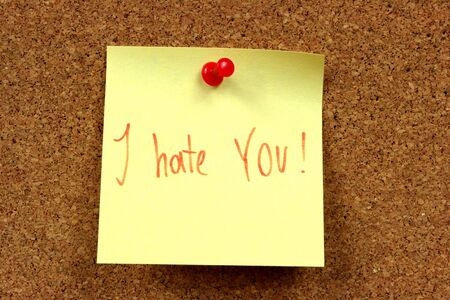 reluctance: Yellow small sticky note on an office cork bulletin board. Hate message. Anger and hatred.