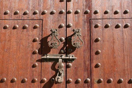 Wooden door of a church in Almeria, Spain. Old architecture - knocker, bolt, padlock. Stock Photo - 4070971