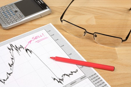 remark: Stock market candle charts, remarks with a red marker, glasses and mobile smart phone