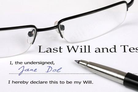 Última Voluntad y Testamento de ficción con un nombre y firma. Vasos, el documento, pluma. Foto de archivo