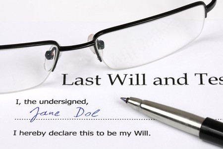 the inheritance: Last Will and Testament with a fictional name and signature. Glasses, document, pen.