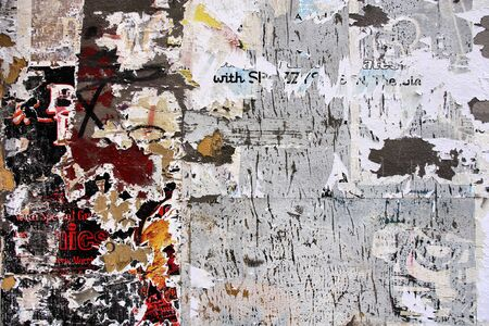 urban decline: Torn posters on old wall, signs of graffiti, vandalism and urban decay Stock Photo
