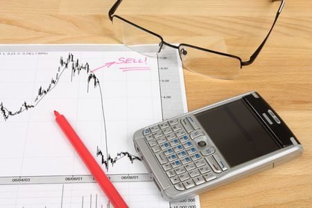 Stock market candle charts, remarks with a red marker, glasses and mobile smart phone photo