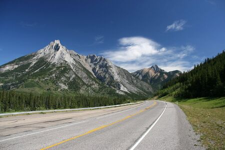 rocky road: Kananaskis Country - Highwood Trail road and Rocky Mountains in summer. Alberta, Canada. Stock Photo
