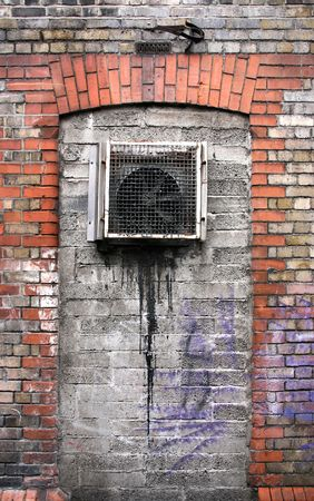 Grunge wall with old fan and graffiti stains. Urban decay and vandalism. Stock Photo - 4822853